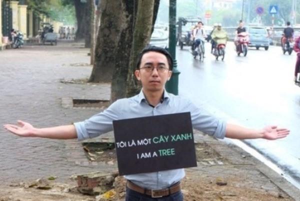 Chàng trai đeo biển 'tôi là một cây xanh' bên hố cây bị chặt