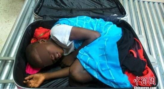 Bé trai 8 tuổi nằm trong hành lý du lịch