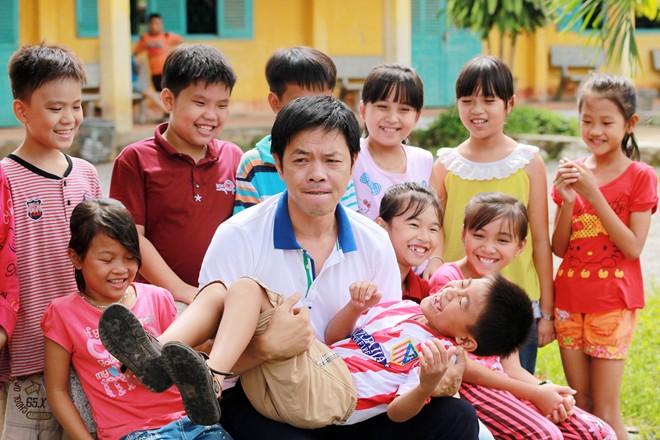 Thái Hòa bế bổng các em nhỏ trong chuyến đi từ thiện