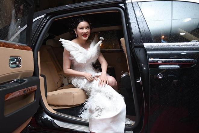 Lý Nhã Kỳ đi xe sang, mặc váy chim công