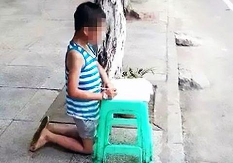 Đạt điểm kém, con bị mẹ bắt quỳ làm bài tập trên phố