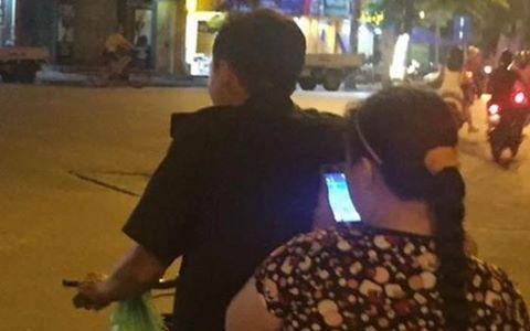 Chồng đèo vợ bằng xe đạp đi bắt Pokemon trên phố