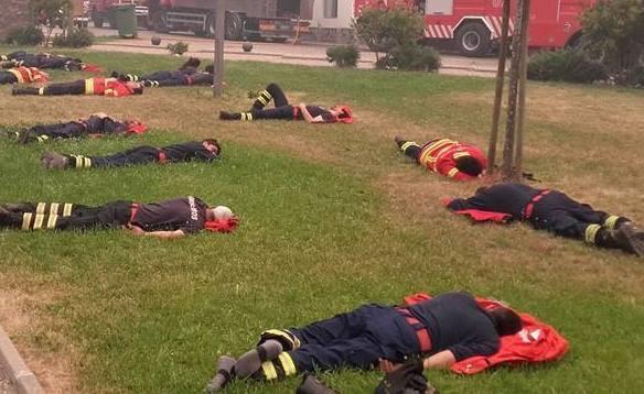 Lính cứu hỏa kiệt sức, nằm ngủ trên cỏ sau 24 giờ dập lửa