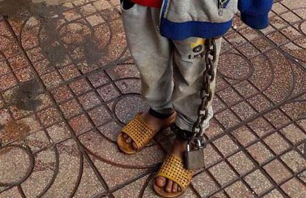 Bé trai bị bố mẹ xích tay chân lang thang giữa chợ