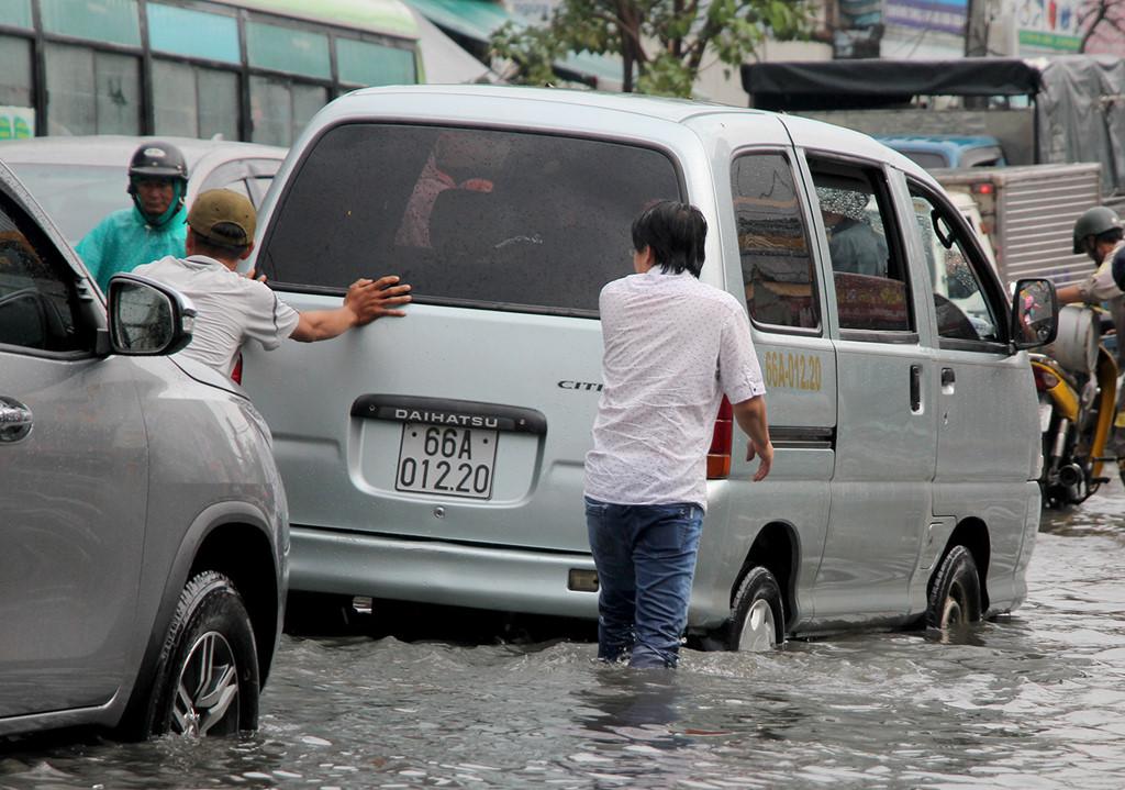 Đẩy ôtô chết máy trong mưa lớn kèm triều cường ở Sài Gòn