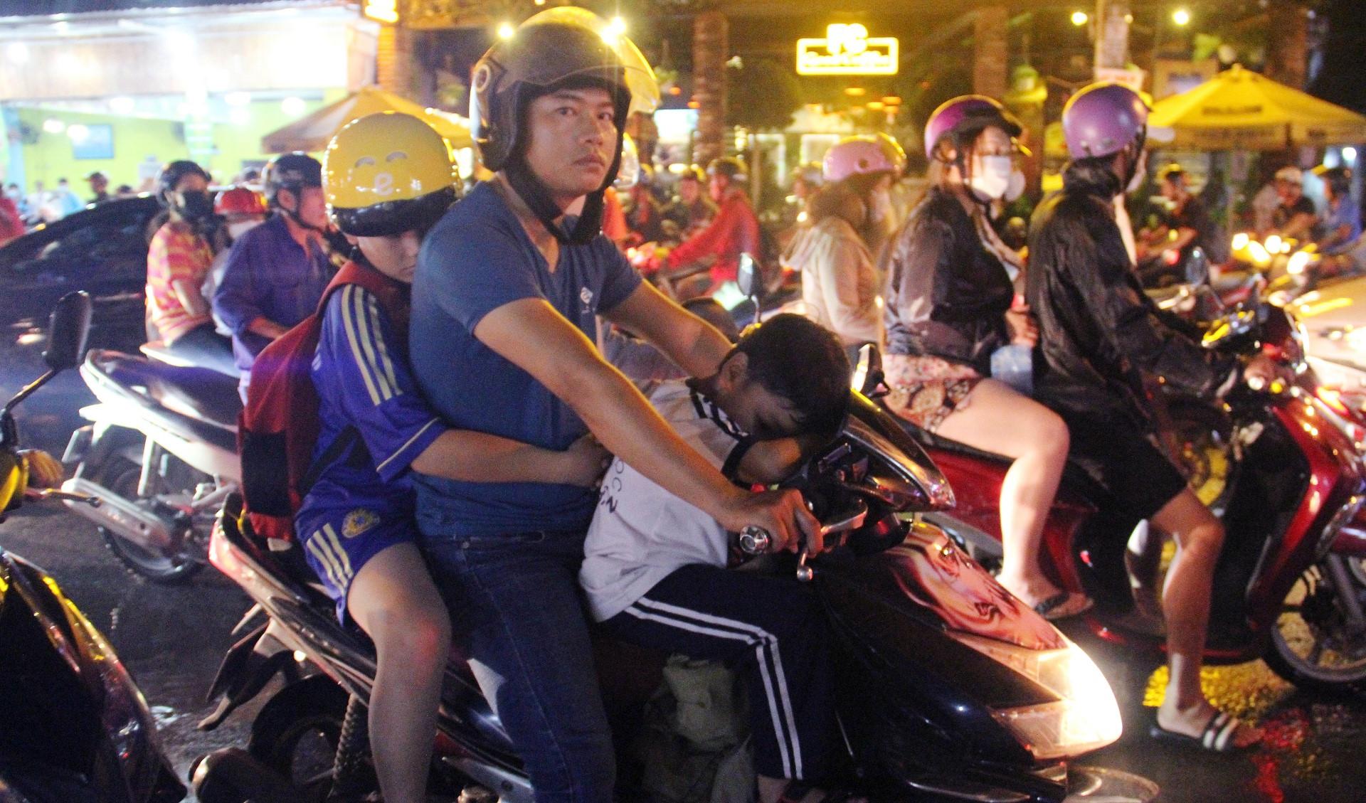 Kẹt xe nhiều giờ ở TP.HCM, trẻ em ngủ gục trên xe máy