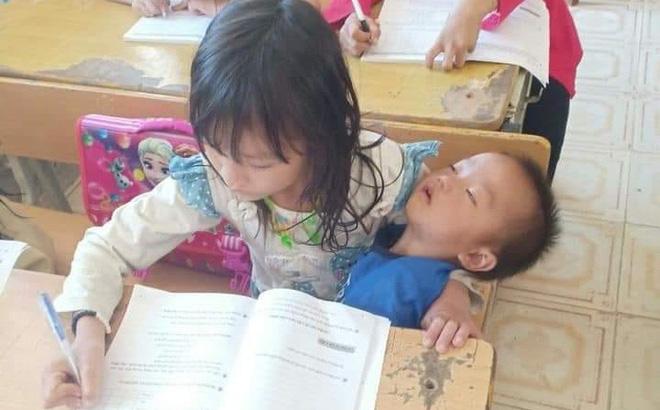Bé gái vừa viết bài vừa bế em ngủ say trên tay khiến CĐM xót xa