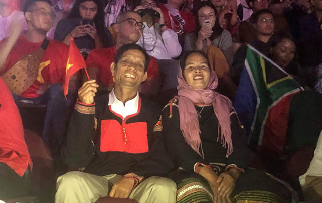 Bố mẹ H'Hen Niê diện trang phục dân tộc Ê Đê, ngồi dưới cổ vũ con gái