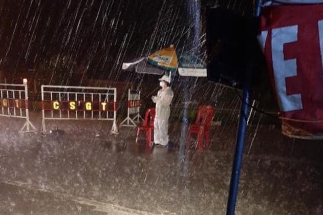 Nữ cán bộ y tế đứng ở chốt chống dịch dưới cơn mưa lớn