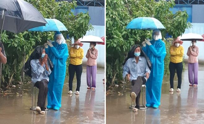 Nữ tình nguyện viên ở TP.HCM cầm ô che cho cụ già dưới trời mưa lớn