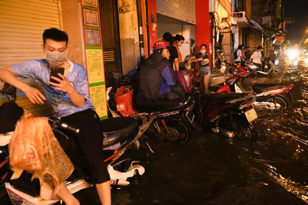 Người Hà Nội đỗ xe lên vỉa hè chờ nước rút sau mưa ngập