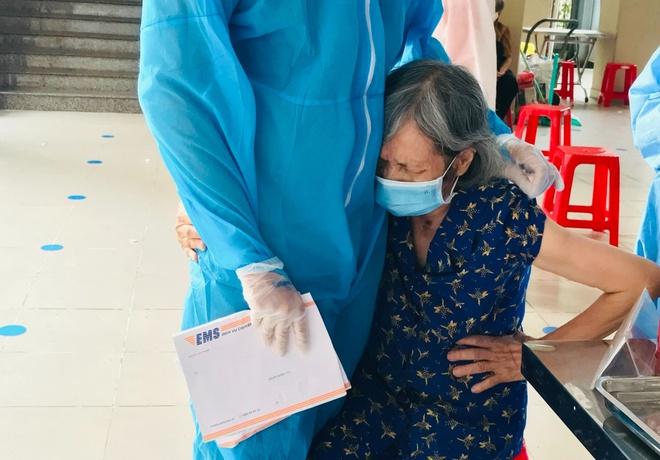 Tình nguyện viên ở TP.HCM cho cụ bà ôm để đỡ sợ khi tiêm vaccine